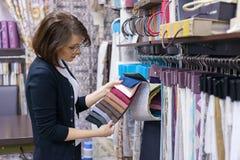 Kvinnaformgivaren, dekoratör väljer tyger för gardiner, kuddar som broderar tyger, mattor i textilshowrummet Royaltyfri Fotografi