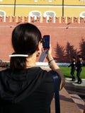 Kvinnafors med mobiltelefonen Arkivfoton