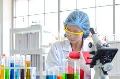 Kvinnaforskare som gör kontrolllistan experimentet royaltyfri fotografi