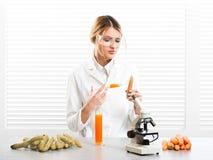 Kvinnaforskare som injicerar grönsaker med syntetiska vikter, färg, vitamin royaltyfri fotografi