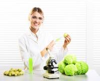 Kvinnaforskare som injicerar kål med syntetiska vikter för tillväxt royaltyfri bild