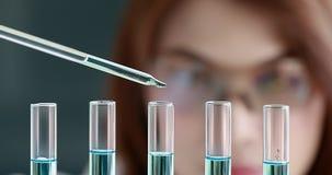 Kvinnaforskare som tappar flytande in i provr?r arkivfilmer