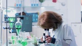 Kvinnaforskaren använder ett mikroskop lager videofilmer