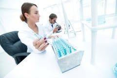Kvinnaforskaren omges av medicinska små medicinflaskor och flaskor Royaltyfri Bild