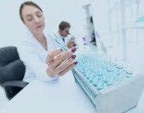 Kvinnaforskaren omges av medicinska små medicinflaskor och flaskor Royaltyfri Fotografi
