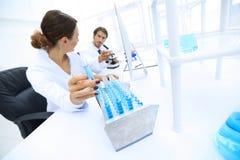 Kvinnaforskaren omges av medicinska små medicinflaskor och flaskor Royaltyfria Foton