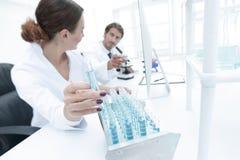 Kvinnaforskaren omges av medicinska små medicinflaskor och flaskor Arkivbilder