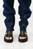 Kvinnafot i de tjocka sandalerna Arkivbild