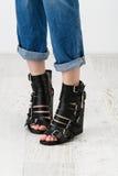 Kvinnafot i de tjocka sandalerna Royaltyfri Foto