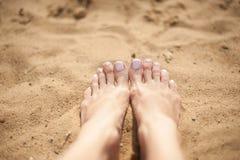 Kvinnafot med ljus - rosa tånaglar på sanden Royaltyfri Foto