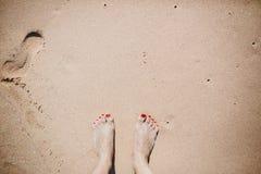 Kvinnafot på den sandiga stranden Den lyckliga mannen tycker om på ferier på havet Royaltyfri Bild