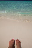 Kvinnafotcloseup av flickan som kopplar av på stranden på den sunbed tyckande om solen på solig sommardag sandig strandfot Royaltyfri Bild