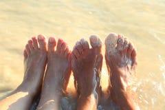 Kvinnafotcloseup av flickan som kopplar av på strand på den sunbed tyckande om sunen på solig sommardag Två par av fot av ett par Royaltyfri Fotografi