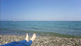 Kvinnafotcloseup av flickan som kopplar av p? strand p? den sunbed tyckande om sunen p? solig sommardag Kvinnafotcloseup av flick arkivbilder