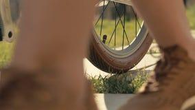 Kvinnafoten som går bredvid ridning, cyklar på stenlagd banaultrarapid stock video