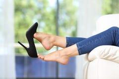 Kvinnafoten som tar av, skor att vila på en soffa arkivbild