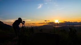 Kvinnafotograf och härlig soluppgång Arkivbilder