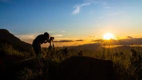 Kvinnafotograf och härlig soluppgång Arkivbild