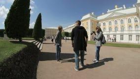 Kvinnafotograf som fotograferar en man i en parkera övreträdgården, Peterhof, St Petersburg, Ryssland lager videofilmer