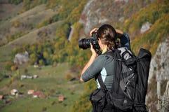 Kvinnafotograf som tar ett foto i bergen på hösten Arkivfoto