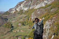 Kvinnafotograf som tar fotoet i bergen Arkivfoto