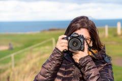 Kvinnafotograf Taking Photos med en utomhus- yrkesmässig Digital kamera royaltyfria foton