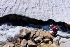 Kvinnafotograf vid Alpine Creek royaltyfria bilder
