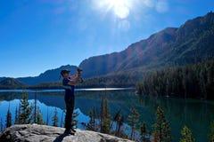 Kvinnafotograf vid den alpina sjön med reflexion i lugna vatten arkivfoton