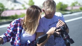 Kvinnafotomodell och fotograf som ser fotoet på kamera medan fotoperiod Fotograf och ung modemodell arkivfilmer
