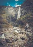 Kvinnafotvandrare med ryggsäckanseende nära den Vettisfossen vattenfallet Arkivfoto