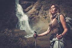 Kvinnafotvandrare med ryggsäckanseende nära den Vettisfossen vattenfallet Royaltyfria Foton