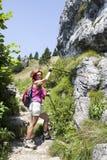 Kvinnafotvandrare som är hög i berget som pekar till teckenstolpen royaltyfria bilder
