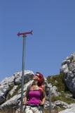 Kvinnafotvandrare som är hög i berget som vilar under teckenstolpen fotografering för bildbyråer