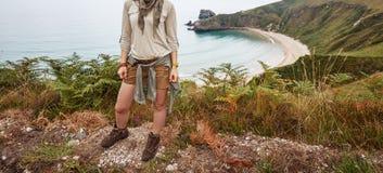 Kvinnafotvandrare som åt sidan framme ser av landskap för havsikt Royaltyfri Foto
