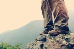 Kvinnafotvandrare som fotvandrar på bergmaximumet royaltyfri fotografi