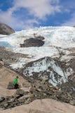 Kvinnafotvandrare som går i Franz Josef Glacier arkivfoton