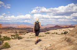 Kvinnafotvandrare som går med ryggsäcken i berg Arkivfoto