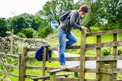 Kvinnafotvandrare som klättrar över ett staket på en Sunny Spring Day royaltyfri foto