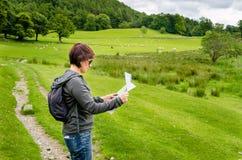 Kvinnafotvandrare som kontrollerar en översikt arkivfoton
