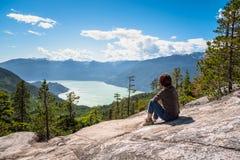Kvinnafotvandrare som kopplar av på överkanten av ett berg och beundrar det sceniska landskapet royaltyfri bild