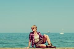 Kvinnafotvandrare som kopplar av på havskust Royaltyfria Bilder