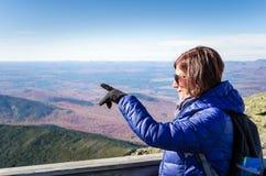 Kvinnafotvandrare som pekar på det ursnygga landskapet royaltyfria bilder