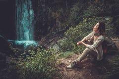 Kvinnafotvandrare som sitter nära vattenfallet i djup skog Arkivfoto