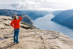 Kvinnafotvandraren på predikstolen vaggar/Preikestolen, Norge royaltyfri fotografi