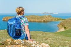 Kvinnafotvandraresammanträde på kusten Royaltyfria Bilder