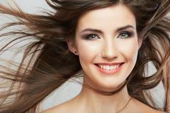 Kvinnaframsida med hårrörelse på vit bakgrund Arkivbild