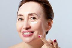 Kvinnaframsida med skrynklor och kräm- slut för skönhetsmedel upp Collagen och anti-åldras begrepp royaltyfri foto