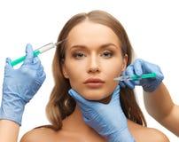 Kvinnaframsida- och kosmetologhänder Royaltyfri Fotografi