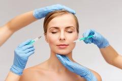 Kvinnaframsida- och kosmetologhänder med injektionssprutan Arkivfoton