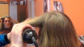 Kvinnaframsidan i spegel- och frisörhänder gör hår att klä stock video